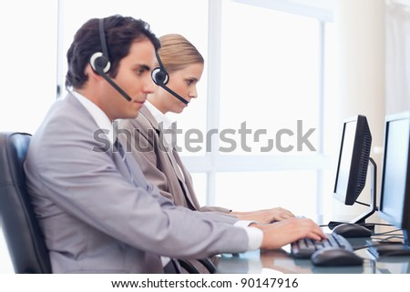 Young operators using a computer in a call center - stock photo