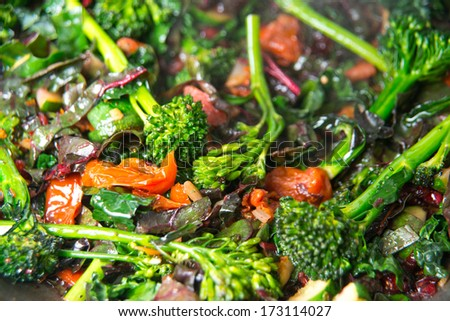 Young Organic Broccolini Lightly Cooked with Zucchini, Onions, Cranberries, and Greens for Healthy Meal - stock photo