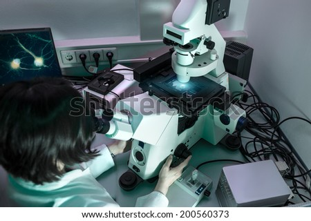 Young oriental scientist works with modern inverted microscope  - stock photo