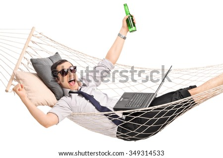 Young overjoyed businessman lying in a hammock with a beer in his hand and working on a laptop isolated on white background - stock photo