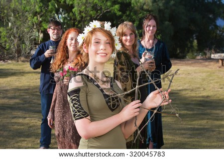 Young pagan woman with group holding a stick pentagram - stock photo