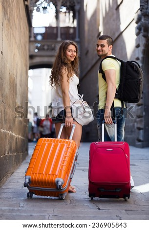young pair in shorts with luggage walking through city street - stock photo