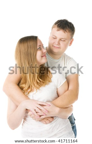 young pair in white T-shirts, the man embraces the girl, isolated on white - stock photo