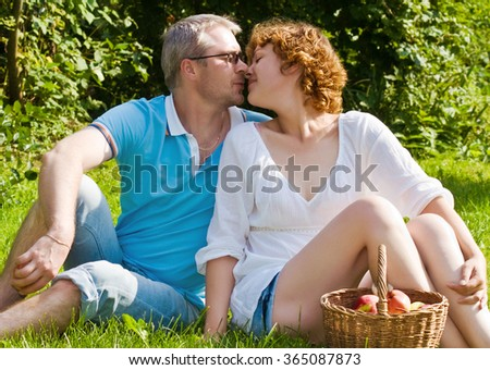 young pair kisses, sitting on a grass - stock photo