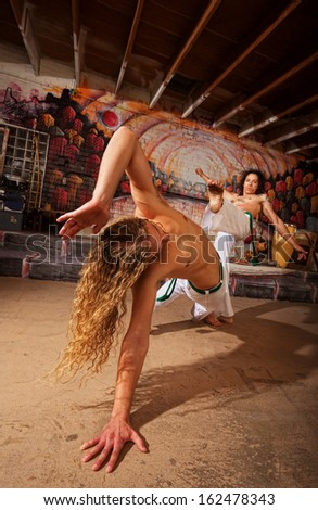 Young pair of capoeira fighting in urban basement - stock photo