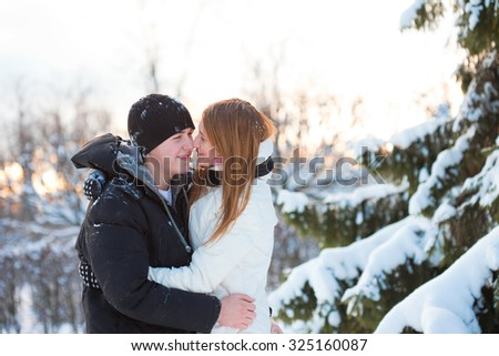 young pair walks in wood, guy and the girl close embracing near snowy spruce - stock photo