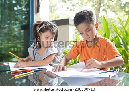 Young pan asian boy with his curious younger sister enjoying drawing and coloring on paper in a home environment - stock photo