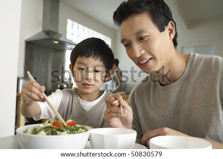 Young parent sitting at table, watching son trying to use chopsticks - stock photo