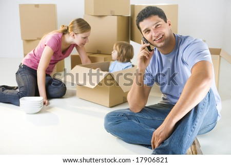 Young parents and their daughter sitting beside cardboard boxes. Young girl sitting in box. They're smiling. A man talking by cellphone and looking at camera. Focused on man. - stock photo