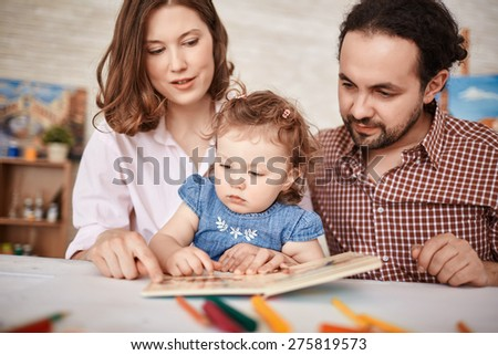 Young parents and their small daughter reading together - stock photo
