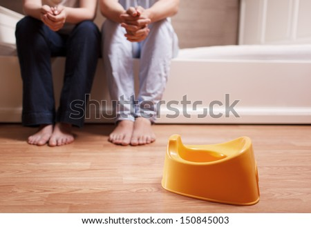 Young parents are sitting on the bed and thinking how to teach kid to use children's pot. Shallow depth of field. - stock photo