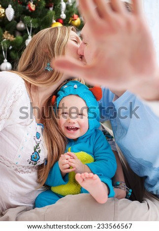 Young parents cover camera with hand while kissing, baby son dressed in little monster costume laughing, Christmas time. - stock photo