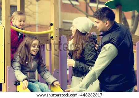 Young parents helping positive little kids on slide in autumn day. Focus on woman - stock photo
