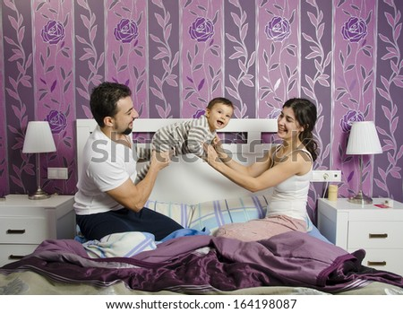 Young parents in home bedroom lifting baby - stock photo