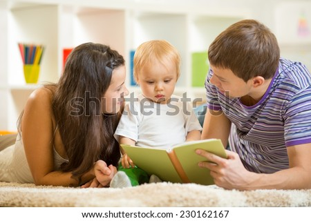 Young parents mom and dad reading children book to baby son - stock photo