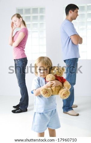 Young parents standing back to back. Theirs daughter huging teddy bear and looking at camera. - stock photo