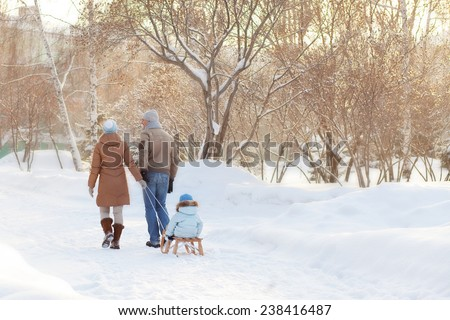 Young parents walking in Winter Park  - stock photo
