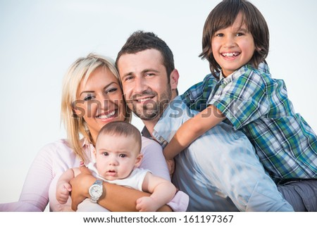 Young parents with a smiling son and a baby posing - stock photo
