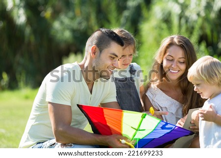 Young parents with children and colorful kite on vacation day.  Focus on man  - stock photo