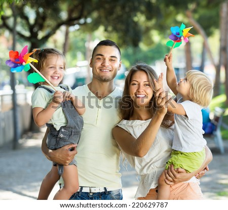 Young parents with children playing windmills in park on vacation day - stock photo