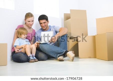 Young parents with daughter sitting on the floor between cardboard boxes. They're looking at laptop. Low angle view. - stock photo