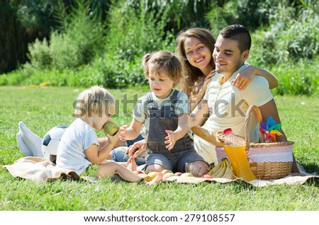 Young parents with little daughters having holiday with picnic in park - stock photo