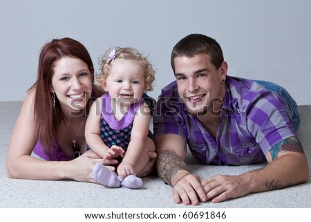 Young parents with one year old baby girl lying on floor. - stock photo