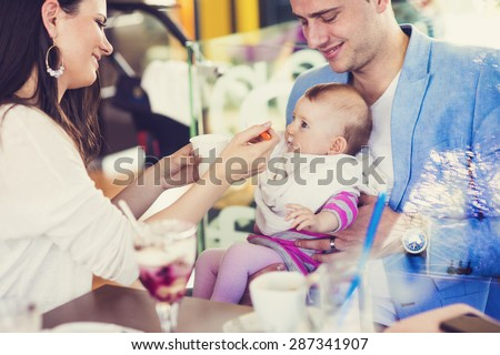 Young parents with their cute baby daughter in cafe - stock photo