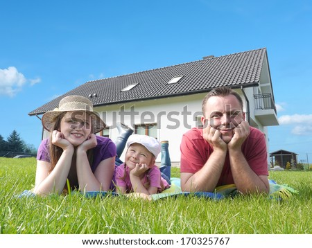 Young parents with their cute little girl lying relaxed on the grass in front of their house - stock photo