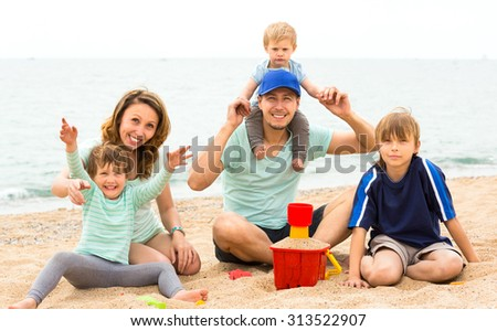 Young parents with three children playing on the coast summer day - stock photo