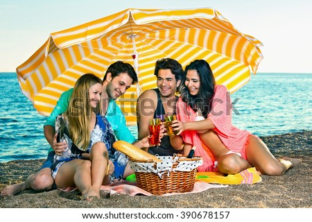 Young party people enjoying during picnic at the beach with bread and wine and healthy fruits and drinks. - stock photo