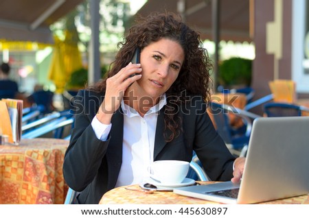 Young pensive businesswoman working at an outdoor cafe as she enjoys coffee while chatting on her mobile phone with her laptop open in front of her - stock photo