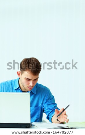 Young pensive casual businessman reading document at office - stock photo