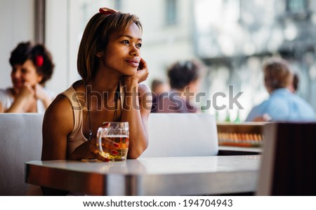 Young pensive woman drinking beer in a bar - stock photo