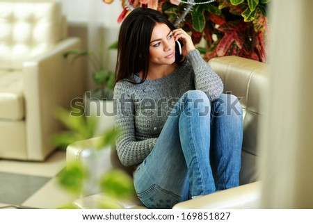 Young pensive woman talking on the phone and looking away at home - stock photo