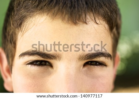 Young people and emotions, portrait of serious kid looking at camera. Closeup of eyes - stock photo