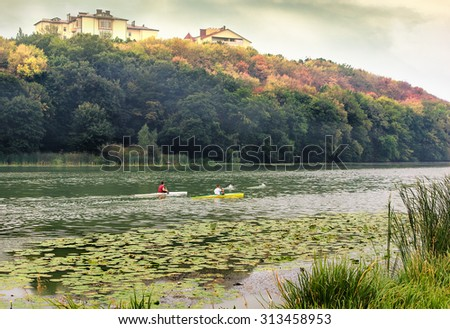 Young people are kayaking on a river in beautiful autumn nature. - stock photo