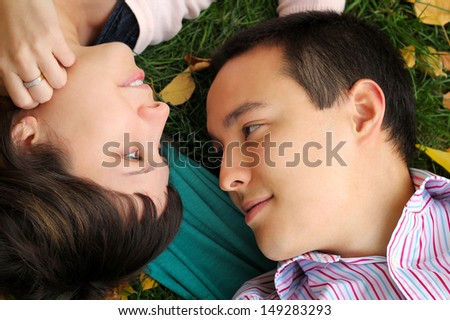 Young people are lying on the grass and look at each other - stock photo