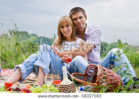 Young people at the picnic.  Portrait of a smiling romantic young couple lying at park - stock photo