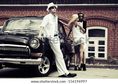 Young people at the retro car - stock photo