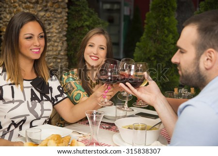 Young people celebrating during a lunch at a restaurant. They are smiling and toasting with wine. - stock photo