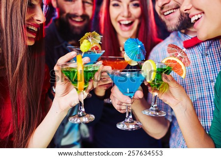 Young people clinking their cocktails - stock photo