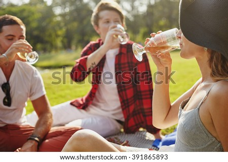 Young people company sittting on the grass in the park for enjoying wing and communication - stock photo