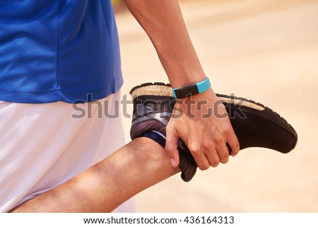 Young people doing sport activities, man runner jogging stretching leg using fit watch. Concept of leisure, health, recreation, fitness, lifestyle, exercising, workout - stock photo