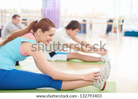 Young people doing stretching in the gym - stock photo