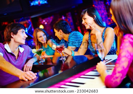 Young people drinking and talking at nightclub - stock photo