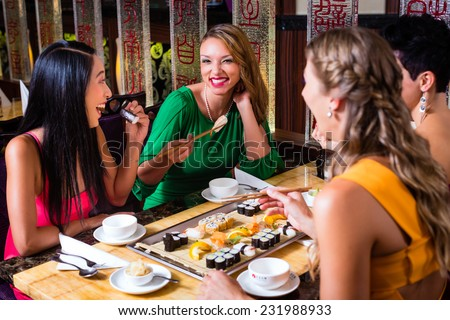 Young people eating sushi in Asian restaurant - stock photo
