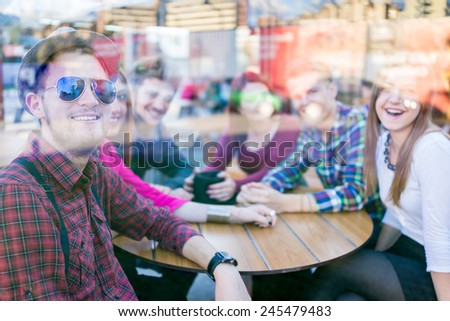 Young people enjoying and having fun (image taken mostly behind glass reflection for desired look) - stock photo