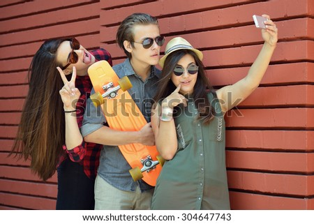 Young people having fun summer outdoor and making selfie with smart phone against red brick wall. Urban lifestyle, happiness, joy, friends, self photo concept. Image toned, noise added. - stock photo