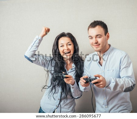 Young people having fun with joystick in the hand - stock photo